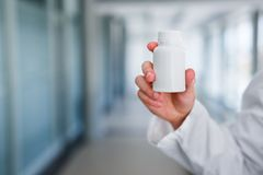 Blank bottle holded by pharmaceut. Blank bottle holding in hand young male doctor while standing at hospital indoor Stock Images