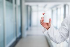 Blank bottle holded by doctor. Blank bottle holding in hand young male doctor while standing at hospital indoor Royalty Free Stock Photos