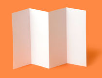 Blank brochure. White blank brochure on orange background Royalty Free Stock Images