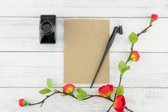 Blank brown card, oblique pen and bottle of ink. Decorated with fake red flowers branches on white wood background Stock Image