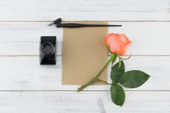 Blank brown card, oblique pen and bottle of ink. Decorated with orange rose on white wood background Royalty Free Stock Photography