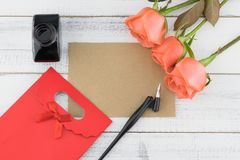 Blank brown card, oblique pen, bottle of ink. And red gift bag decorated with orange roses on white wood background Royalty Free Stock Photography