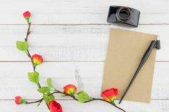 Blank brown card, oblique pen and bottle of ink decorated with fake red flowers. Branches on white wood background with copy space Stock Image