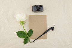 Blank brown card, oblique pen and bottle of ink. Decorated with white rose on white muslin fabric with copy space Royalty Free Stock Image