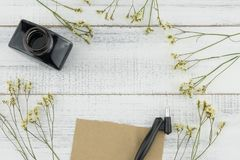 Blank brown card, oblique pen and bottle of ink. Decorated with yellow limonium caspia flowers on white wood background Royalty Free Stock Photo
