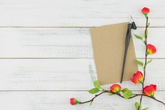 Blank brown card and oblique pen decorated with fake red flowers. Branches on white wood background with copy space Royalty Free Stock Images