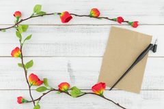 Blank brown card and oblique pen decorated with fake red flowers. Branches on white wood background with copy space Stock Images