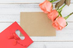 Blank brown card and red gift bag decorated with orange roses Stock Images