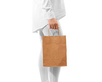 Blank brown craft paper bag design mockup holding hand. Clipping path. Woman hold kraft textured bundle mock up. Clear gift bagful branding template. Shopping royalty free stock photo