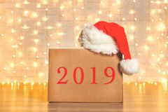 Corrugated fiberboard boxes with christmas lights on background. Blank brown freight box with Santa Claus hat on top, brick wall with Christmas lights on stock photo