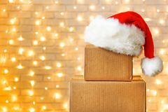Corrugated fiberboard boxes with christmas lights on background. Blank brown freight box with Santa Claus hat on top, brick wall with Christmas lights on stock photos