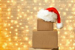 Corrugated fiberboard boxes with christmas lights on background. Blank brown freight box with Santa Claus hat on top, brick wall with Christmas lights on stock images