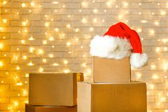 Corrugated fiberboard boxes with christmas lights on background. Blank brown freight box with Santa Claus hat on top, brick wall with Christmas lights on royalty free stock image