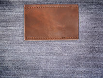 Blank brown leather jean label. Close up blank brown leather jean label over denim background Royalty Free Stock Photos