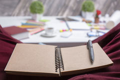 Blank brown notepad on lap. Closeup of brown spiral notepad and pen on man's lap. Blurry messy office desktop in the background. Mock up Stock Image