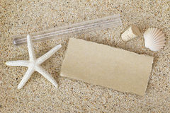 Blank brown paper outside a tube with cork lid removed on a sand Stock Photos
