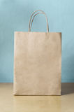 Blank Brown Shopping Bag on Table with Blue Background Stock Image