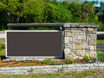 Blank Brown Sign. With log and stone support in a woodsy setting, ready for text Royalty Free Stock Photo