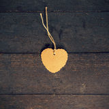 Blank brown tag heart shape on old wood background Stock Images