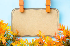 Blank brown tag and wooden clip with yellow leaf. Royalty Free Stock Photos
