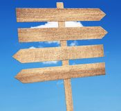Blank brown wooden signpost against blue sky. Royalty Free Stock Image