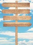 Blank brown wooden signpost against blue sky. Royalty Free Stock Photos
