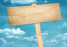 Blank brown wooden signpost against blue sky. Stock Photos