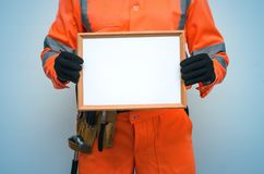Blank builder certificate. Construction diploma. Contractor is showing a blank photo frame border in his hands. Housing project presentation stock photography