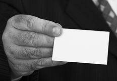 Blank business card. Businessman in suit offering a blank business card. Focus is sharp on the business card Royalty Free Stock Photography