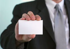 Blank business card. In a hand of a businessman in suit. Space for your own identity or message Royalty Free Stock Photography