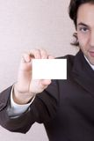 Blank business card. Businessman in a suit holds a blank business card royalty free stock photo