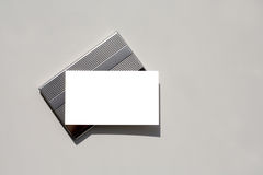Blank business card on holder with clipping path. Blank business card - insert your own text - sitting on silver card holder with grey background which is Royalty Free Stock Image