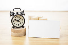 Blank Business card mock up and black alarm clock on light woode Royalty Free Stock Image