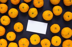Blank business card and orange tangerines on black background. Fresh oranges photo backdrop. White paper card with text place. Citrus fruit top view. Winter Stock Photography