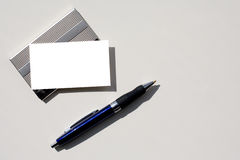 Blank business card and pen with clipping path. Blank business card - insert your own text - sitting on silver card holder with grey background which is perfect Stock Photography