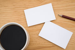 Blank business cards and coffee and pencil. On wooden table Royalty Free Stock Image