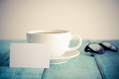 Blank business cards, cup of coffee and eyeglasses on blue woode Royalty Free Stock Images