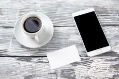 Blank business-cards with cup of coffee and tablet pc smartphone on wooden grunge office desk table. Copy space for your Stock Image