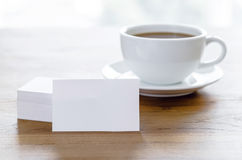 Blank business cards and cup of coffee on wooden table. Stock Image