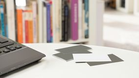 Blank business cards and a laptop in front of a blurred bookshelf. White and grey blank business cards and a laptop on a table in front of a blurred bookshelf in stock photo