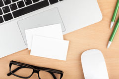 Blank business cards over laptop on office table Stock Photo