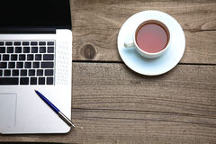 Blank business cards with pen, laptop and tea cup on wooden office table Stock Photography