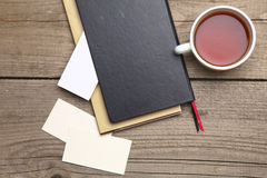 Blank business cards with pen, notebook and tea cup on wooden office table Royalty Free Stock Image