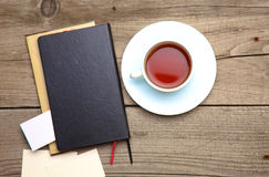 Blank business cards with pen, notebook and tea cup on wooden office table Royalty Free Stock Images