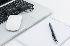 Blank business laptop, mouse, pen, glasses and note Stock Photo