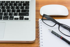Blank business laptop, mouse, pen, note and glasses Stock Images