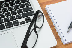 Blank business laptop, mouse, pen, note and glasses Royalty Free Stock Images