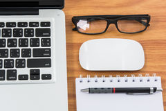 Blank business laptop, mouse, pen, note and glasses Royalty Free Stock Photography