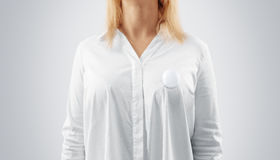 Blank button badge mockup pinned on the womans chest. Girl wear white shirt and campaign pin mock up. Volunteer round emblem design element. Pesron stand front royalty free stock image
