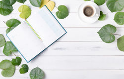 Blank calendar with heart shaped green leaf and coffee. On white wood background, business concept Royalty Free Stock Image